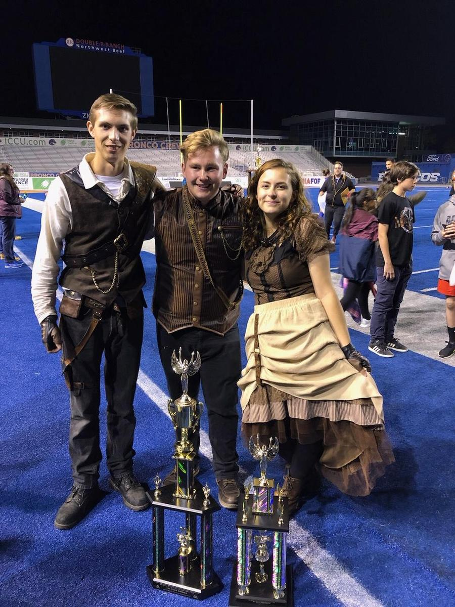 Nampa High student band leaders pose with their trophies on the blue field.