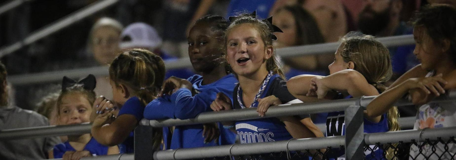 Young students at a varsity football game