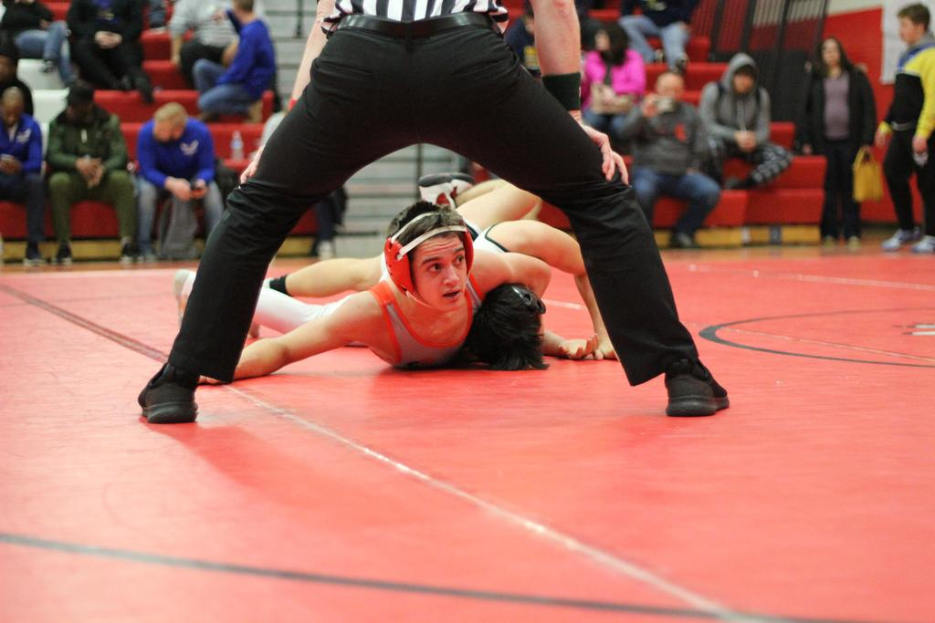 Two athletes wrestling at a meet