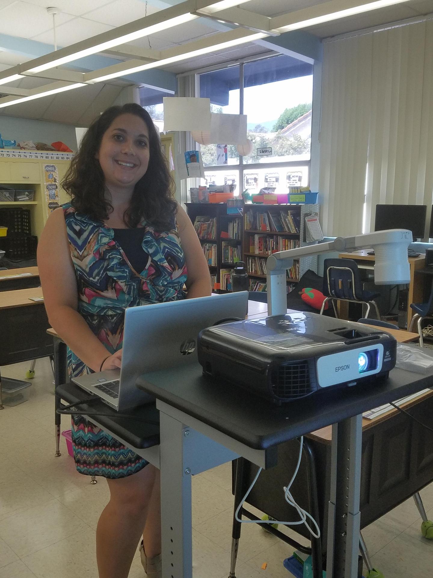 Third grade teacher, Mrs. Wanstrath, standing behind her new computer stand.