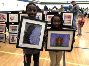 two students proudly hold up their artwork