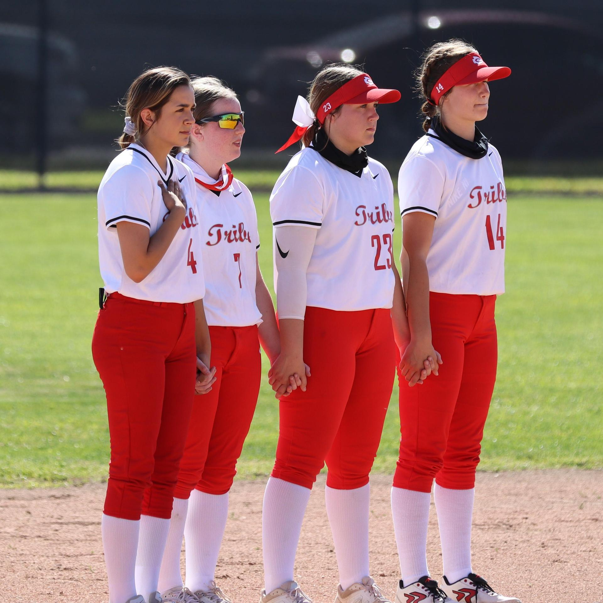 girls standing for the National Anthem before playing softball
