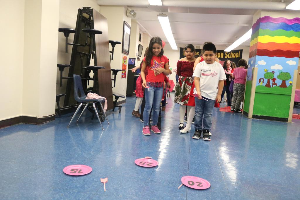 group of kids trying to throw arrows into pink plates with different scores
