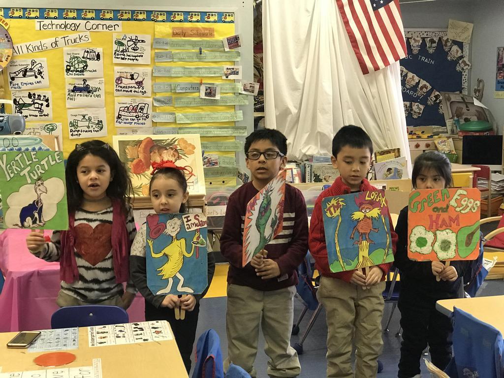 children holding up dr. seuss books