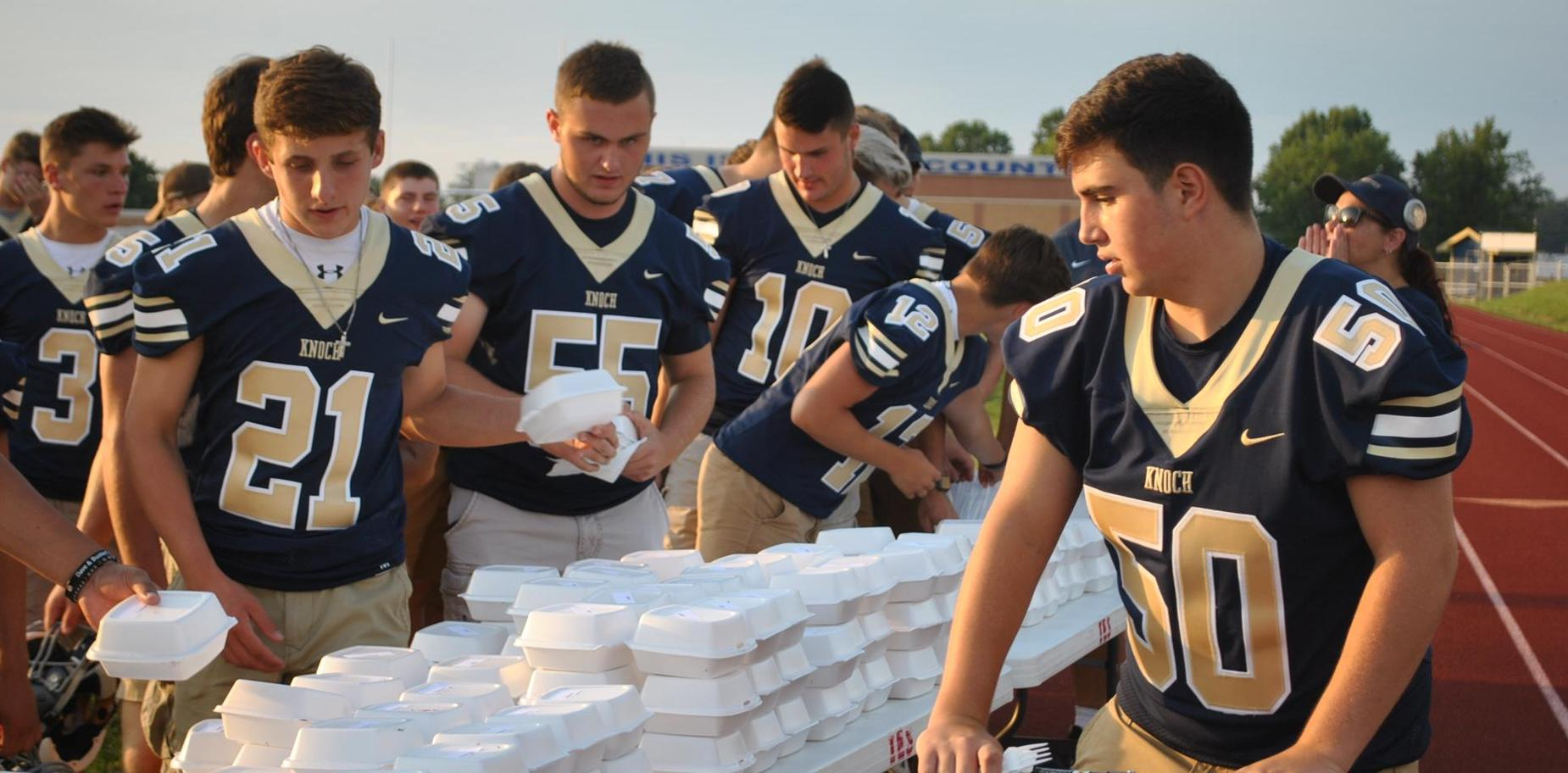 Football players getting pie at Pie Night
