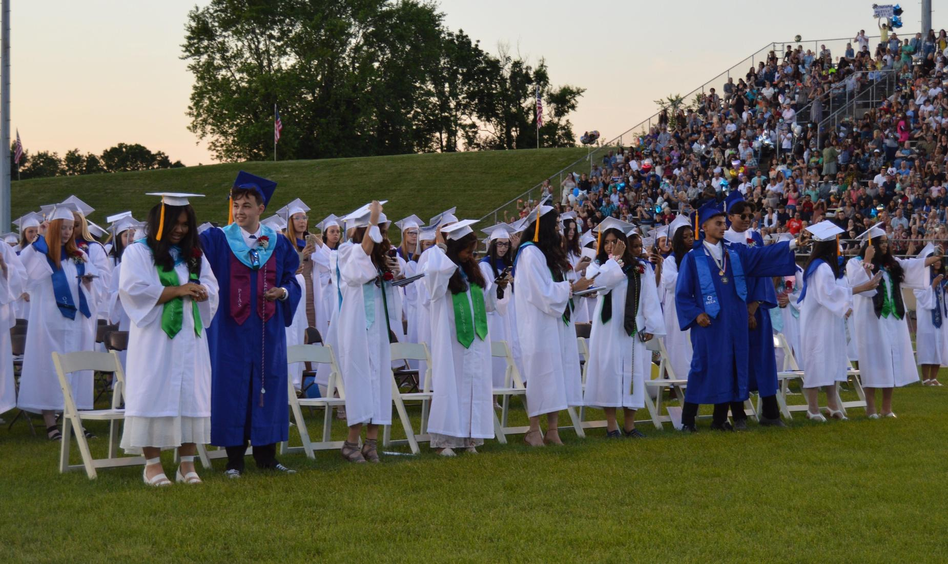 BHS seniors, girls in white gowns and boys in royal blue gowns ready to move their tassel as they are announced as graduates