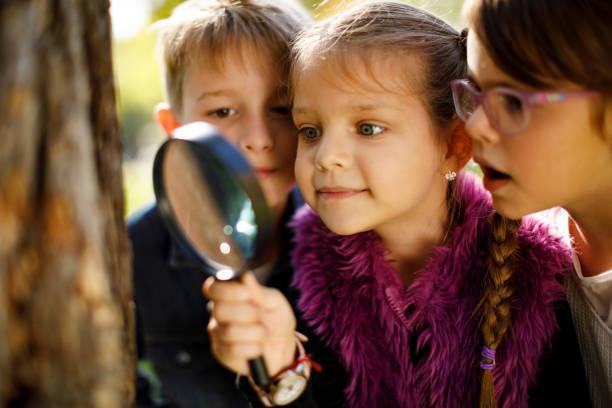 three kids looking through a magnify glass at tree bark