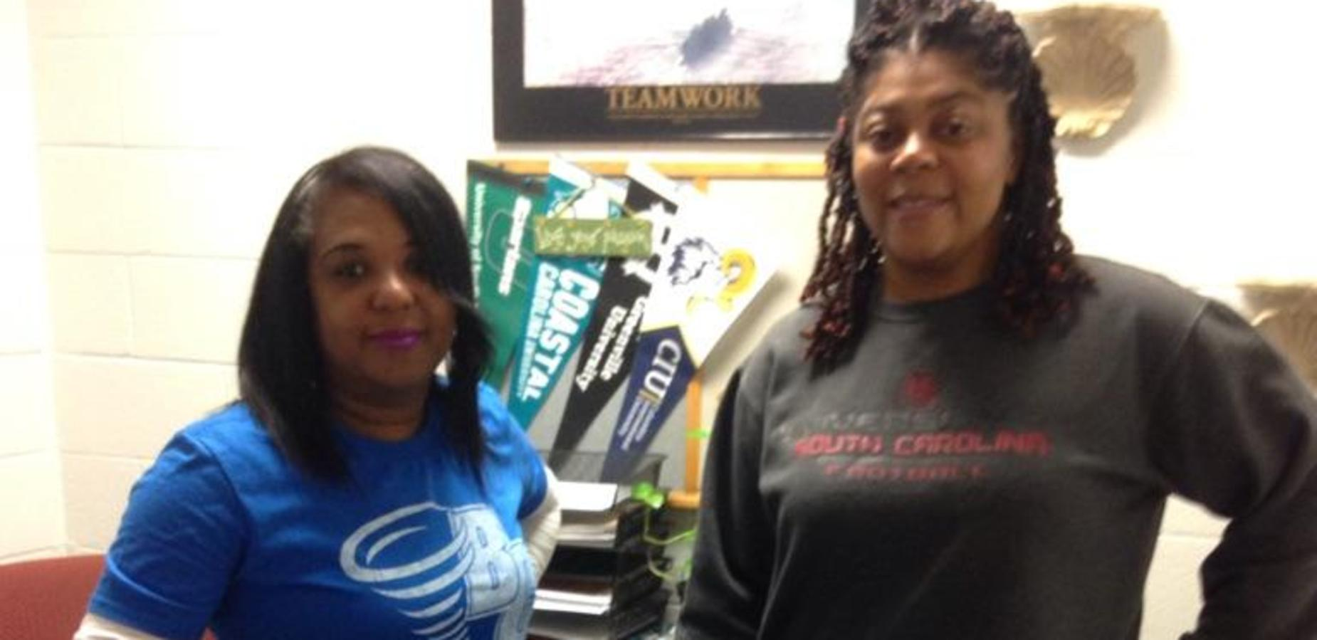 Two staff members wearing college shirts on College Day Wednesday