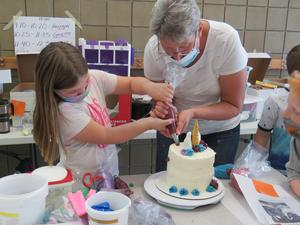 Ranelle Smith helps students try making flowers and decorations using a frosting bag.