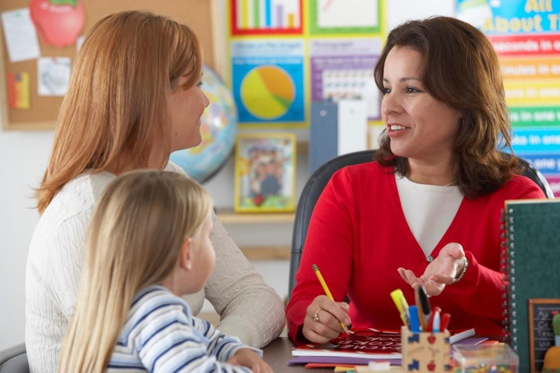 Photo of parent and student speaking with a teacher
