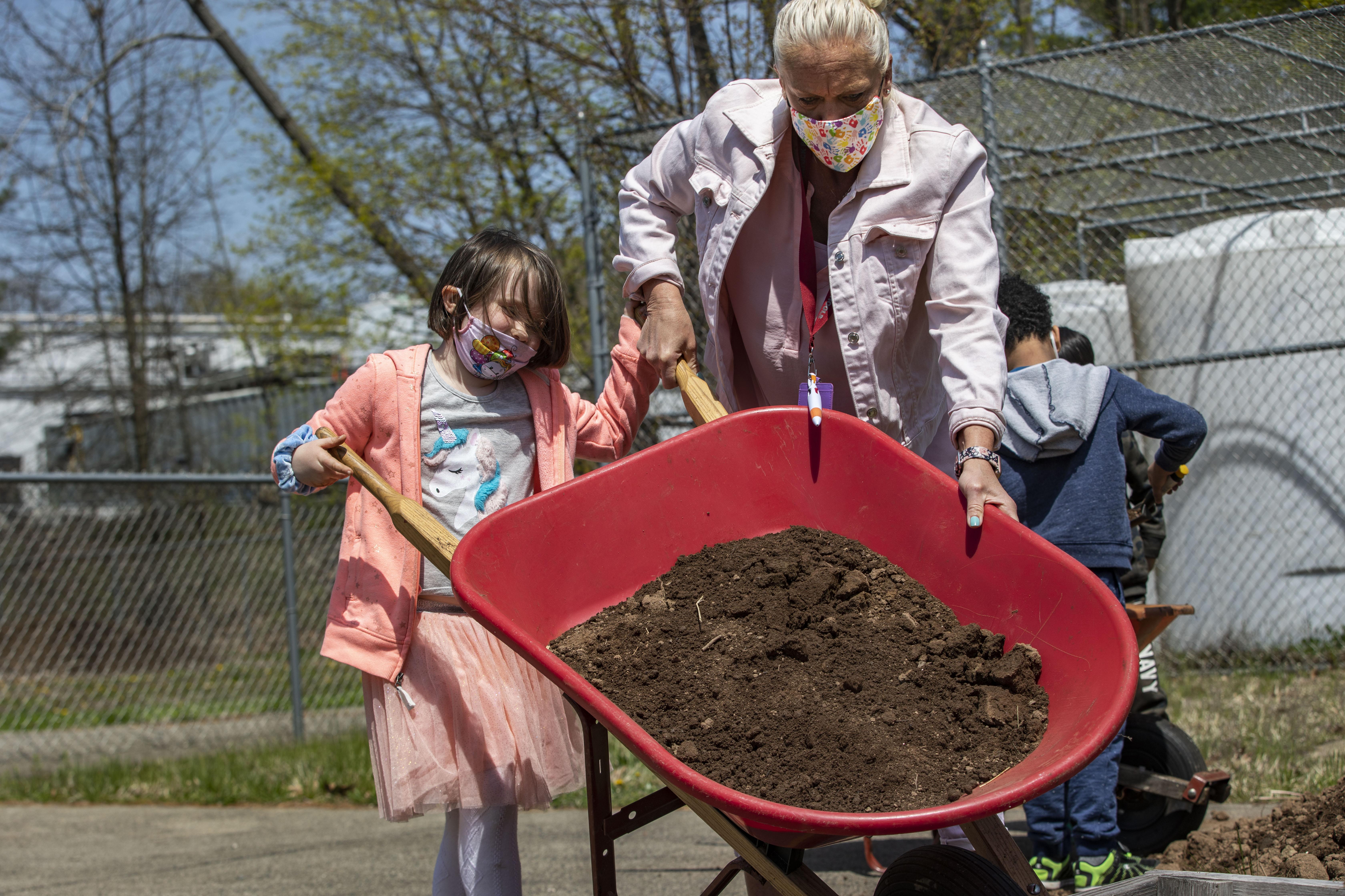 student and teacher dumping dirt into the school garden