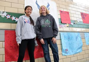 Two Edison Intermediate School students pose for a picture as they hang signs and banners for the school's annual Veterans Day assembly.