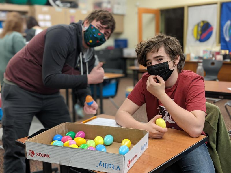 Two students filling eggs with candy
