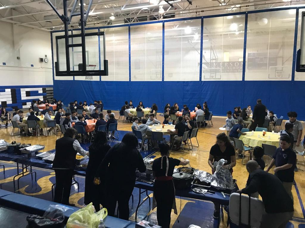 full shot of the celebration in the gym with the tables decorated and students eating while teachers are serving food at the long table