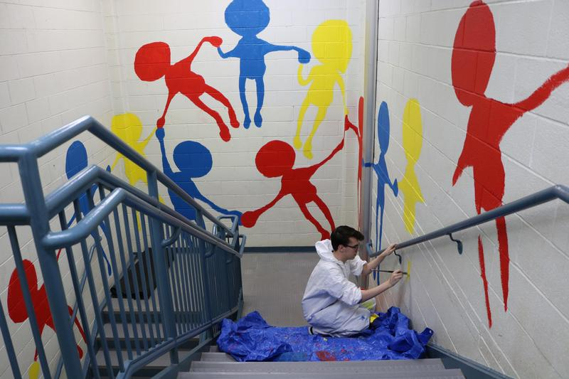 Photo of WHS senior Adam Wachtel working on mural at McKinley School.