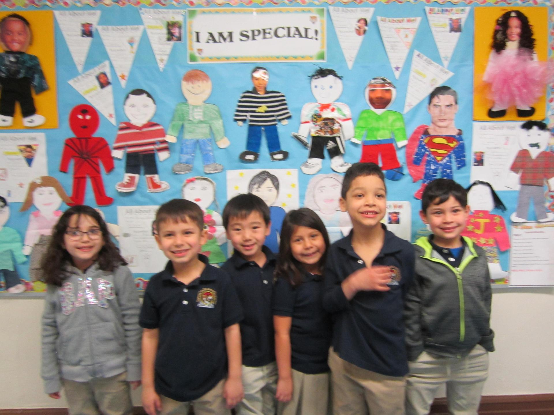 kids showing off the bulletin board they created