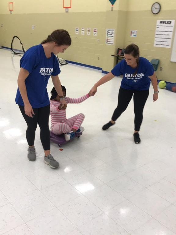 Barton College students drag a student on the floor with wheels under her during P.E. class.