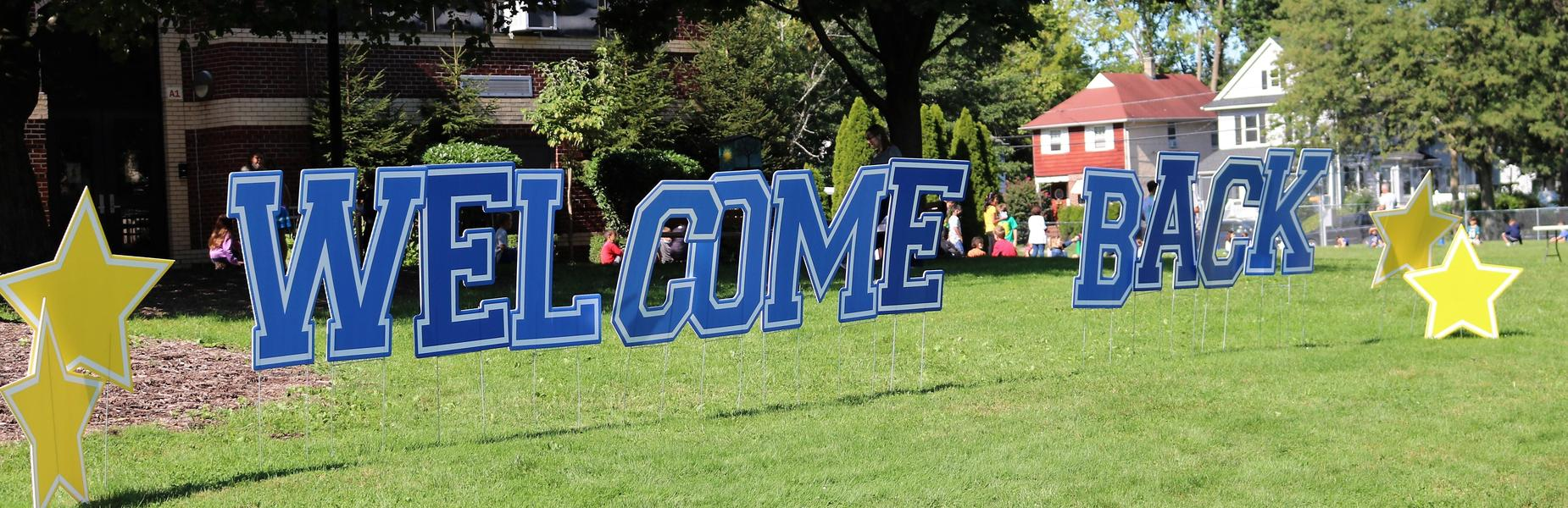 Photo of large Welcome Back sign on school front lawn.