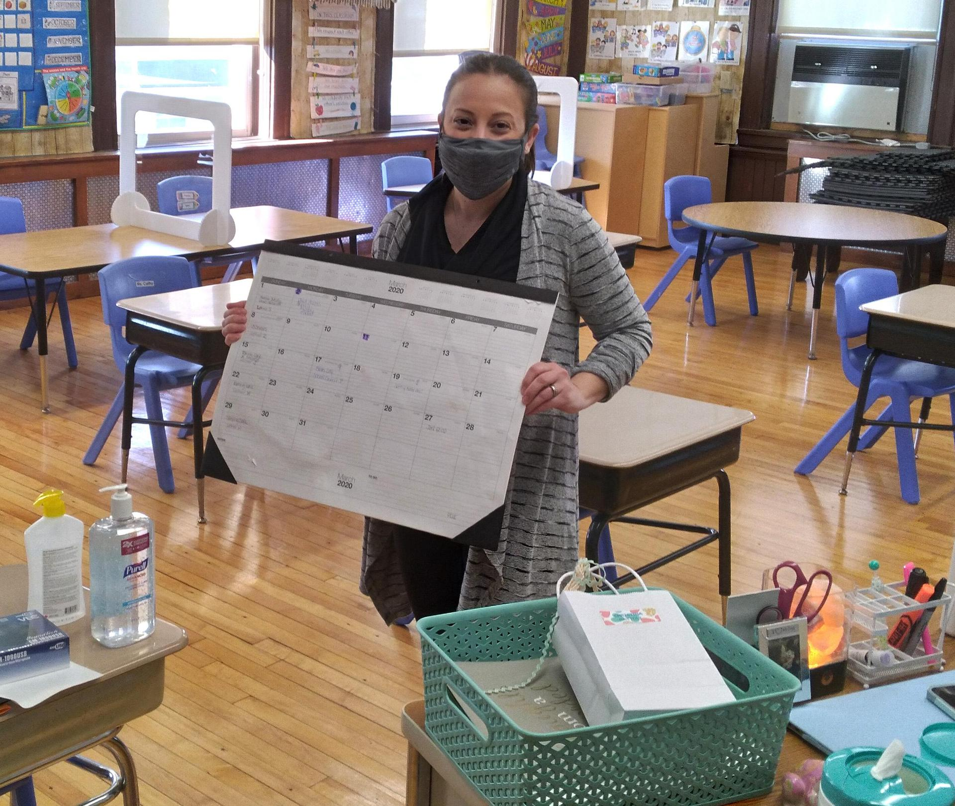 A teacher holding up a desk calendar