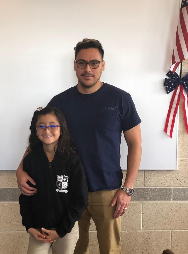 girl proudly stands with her father a navy vet