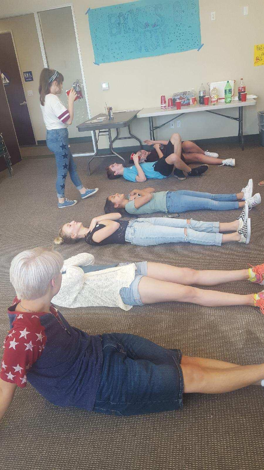 Picture of students laying on the ground following the mystery game