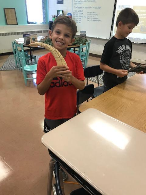 Students smiling while holding a fossil replica