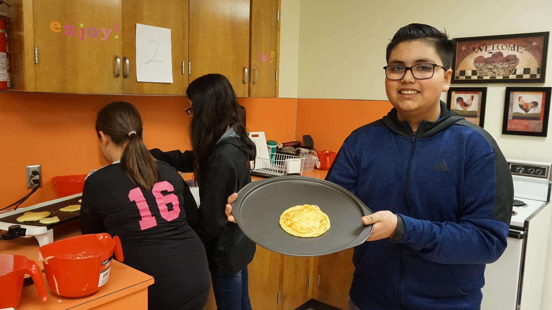 Male student showing his cooked pancake