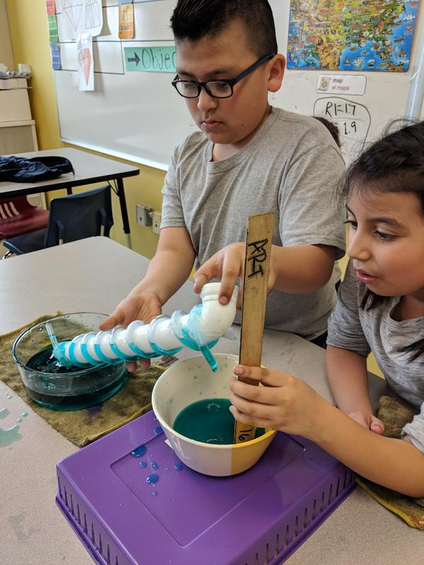 Two students in STEM Explorers use a handheld water pump.