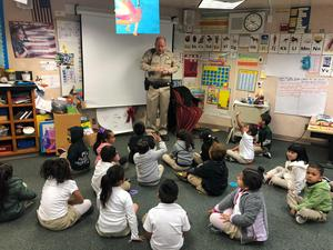 California Highway Patrol Officer reading to a group of students, image 1
