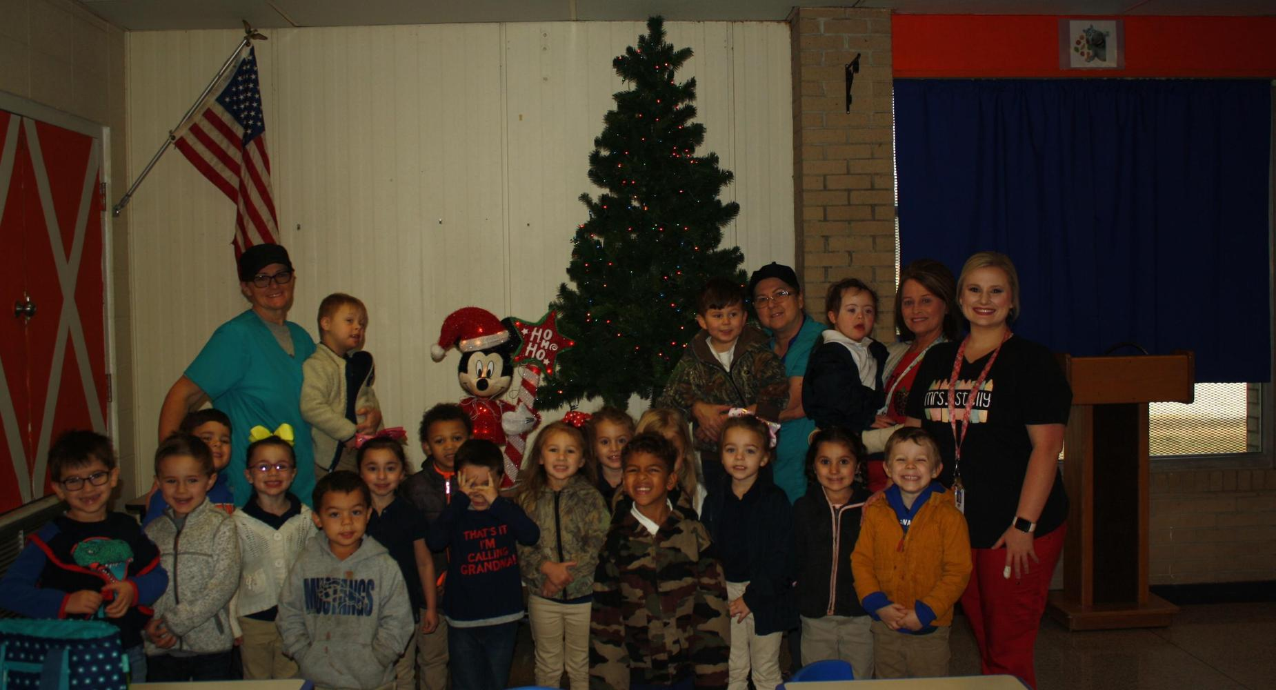 Pre-K students standing next to Christmas tree