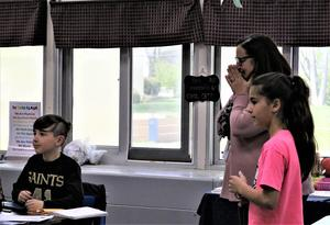 Photo of Philhower Award winner Jefferson 4th grade teacher Anna Carissimo reacting in surprise as she learns of the award.  Two students smile next to her.