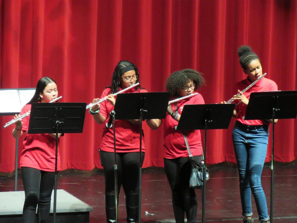 Four female flute players perform at center stage