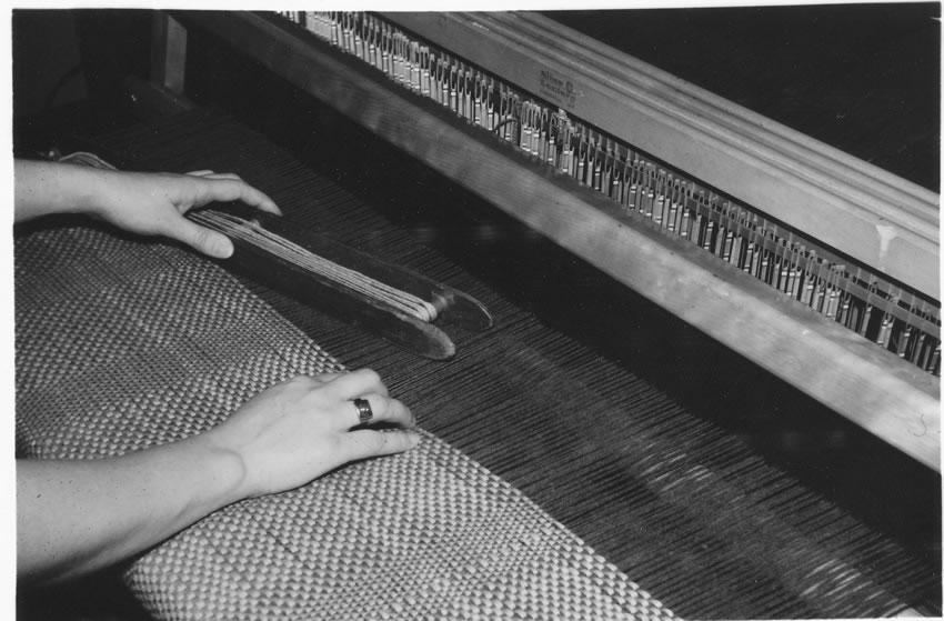 Closeup of a student weaving fabric on a loom.