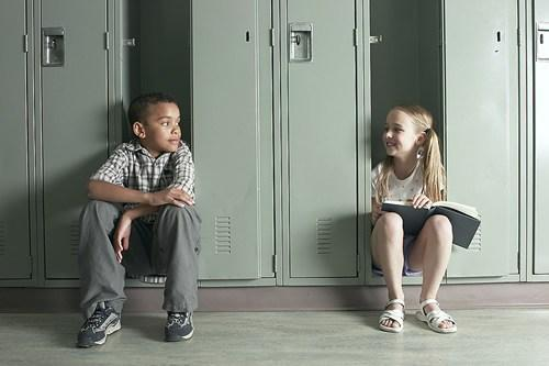 boy and girl sitting by lockers
