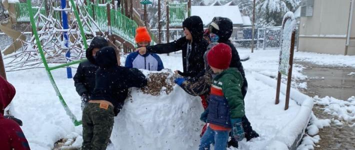 Students playing in snow on playground