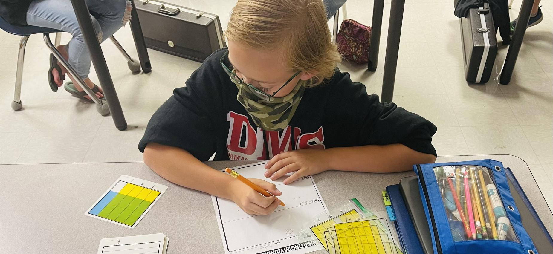 A student works math problems in a classroom.