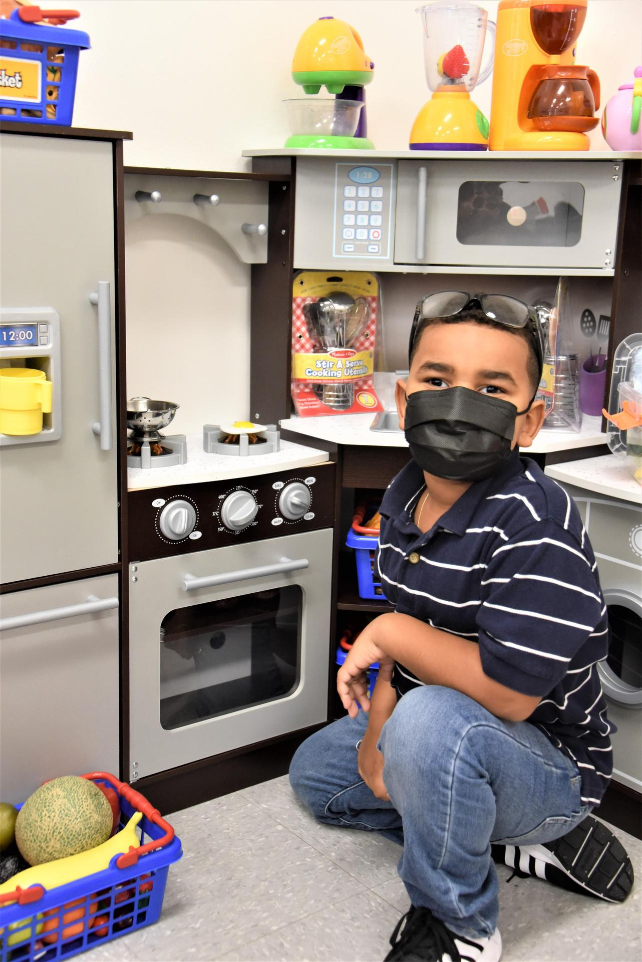 A boy kneels in front of a toy kitchen in a classroom