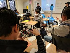 Students and Motiva workers with robots