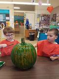 two boys painting a green pumpkin