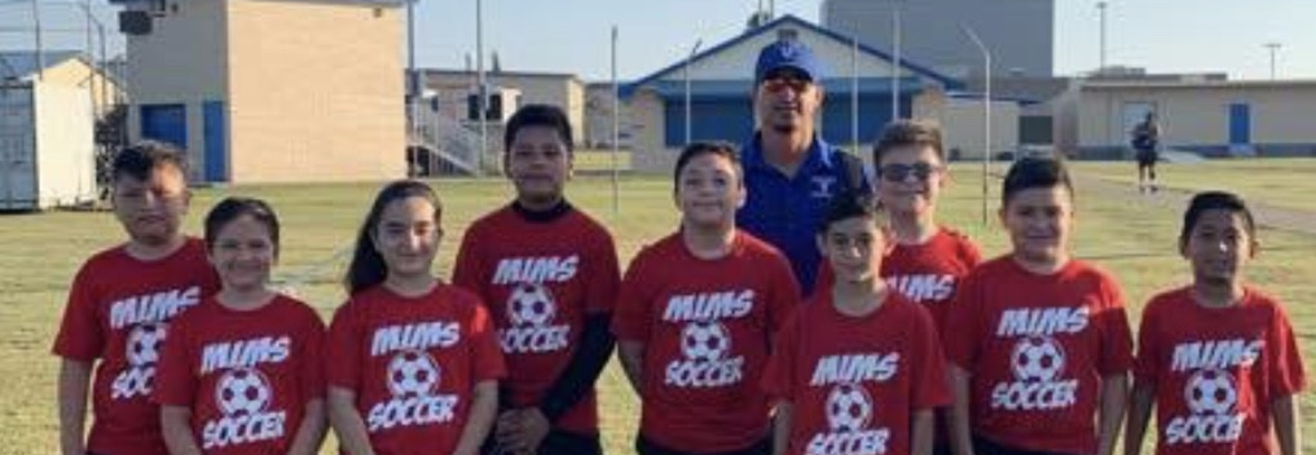 kids and coach wearing soccer shirts