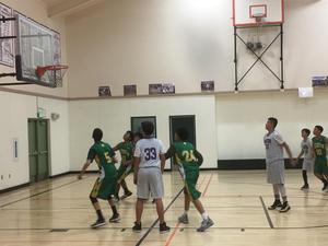 middle school basketball players from two teams looking at free throw shot