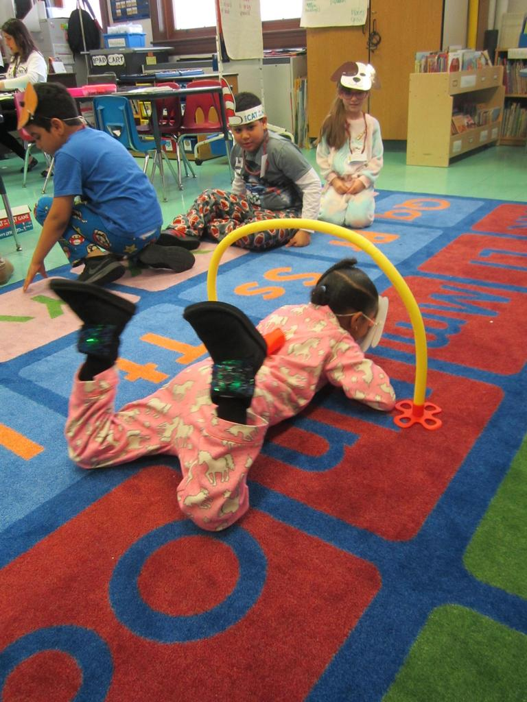 girl wearing pj's on the class rug under a yellow swim noodle in the shape of an arch