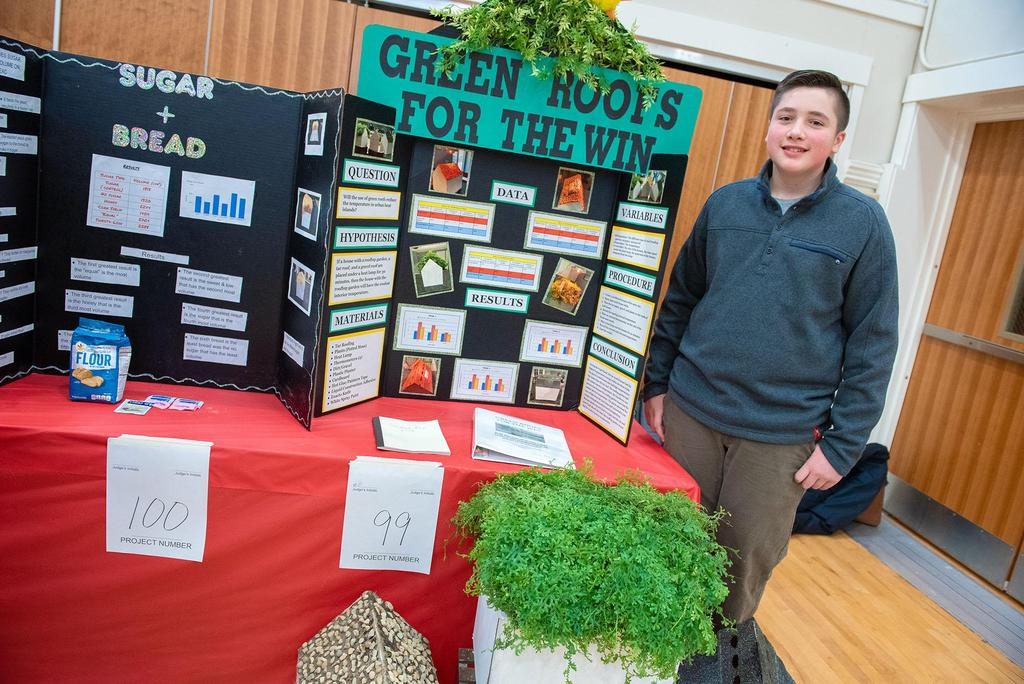 A student stands in front of his project called Green Roofs For The Win