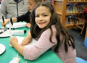 2nd grader tries her hand at calligraphy during Colonial Days at Wilson School.