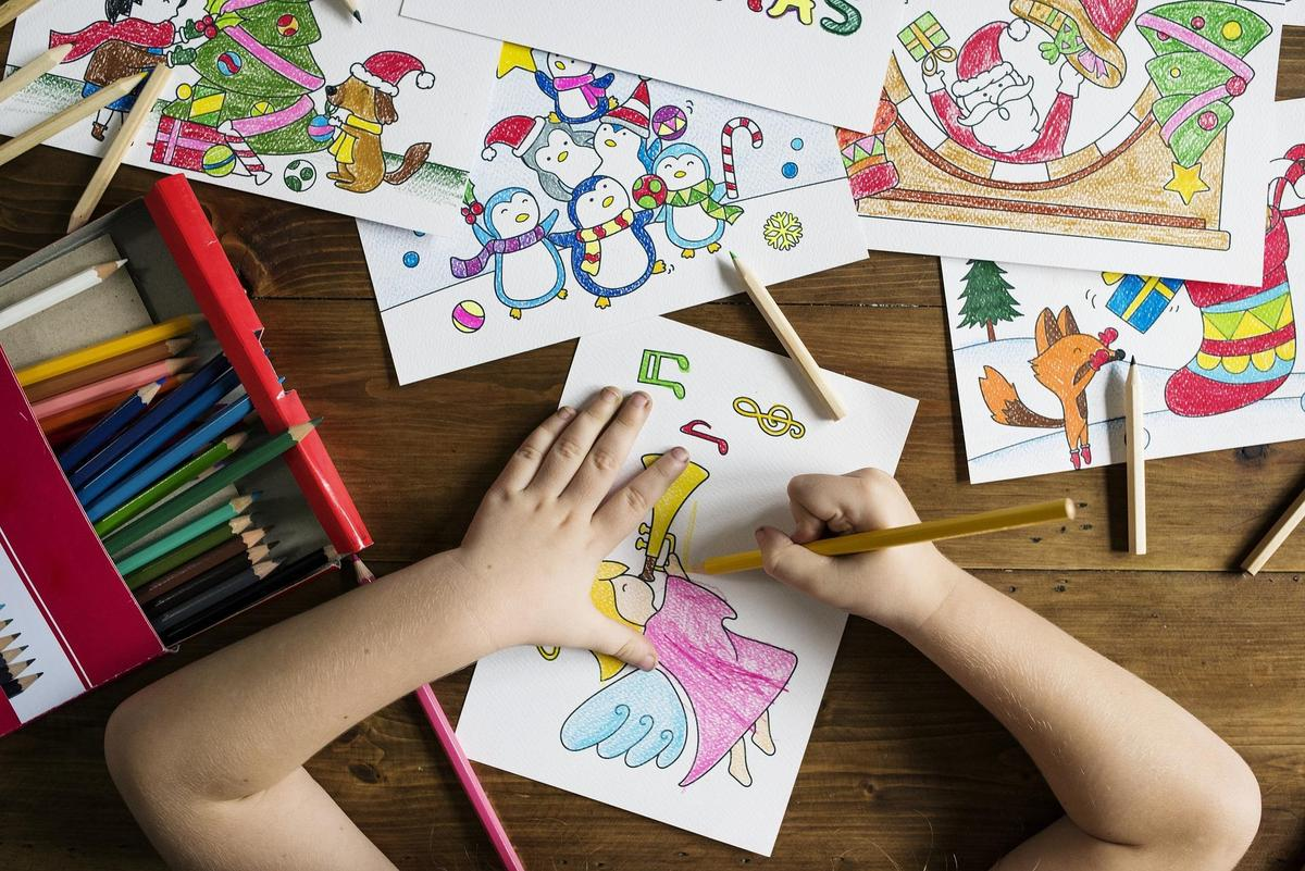 photo of child drawing with colored pencils
