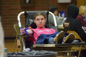 girl giving blood at blood drive in gym