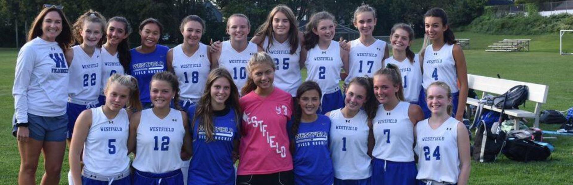 Photo of freshman girls field hockey team as coach celebrates her 100th win.