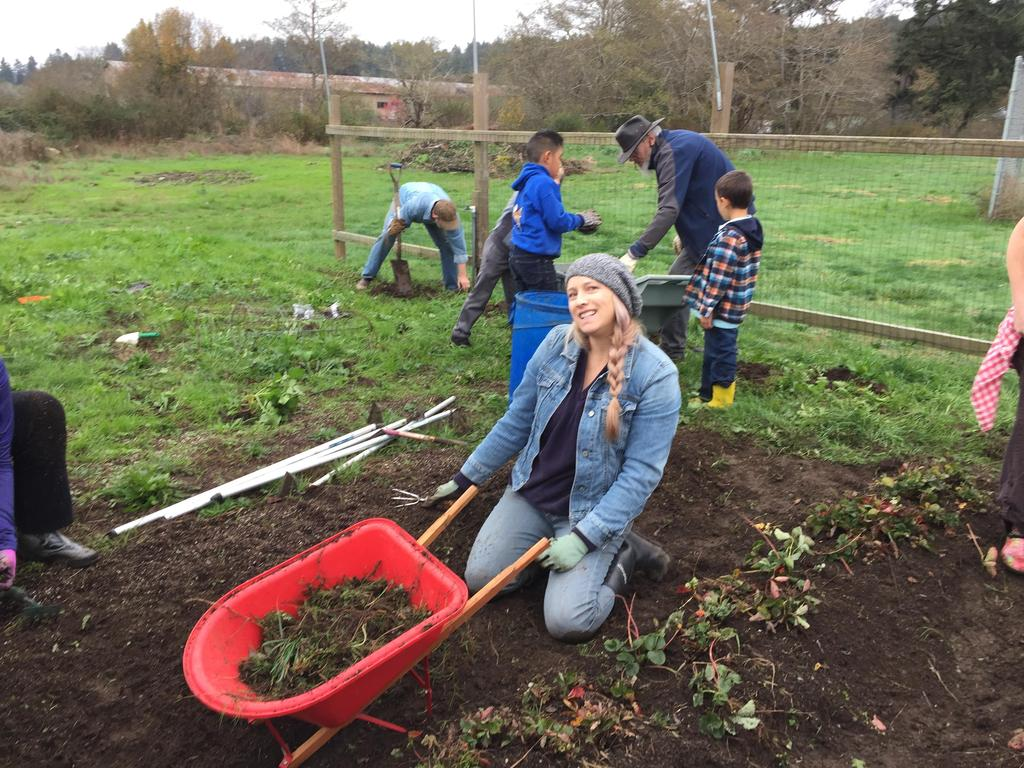 Families helping weed at garden clean-up day
