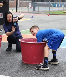 Student at Wilson School has fun with water relay race during Field Day.