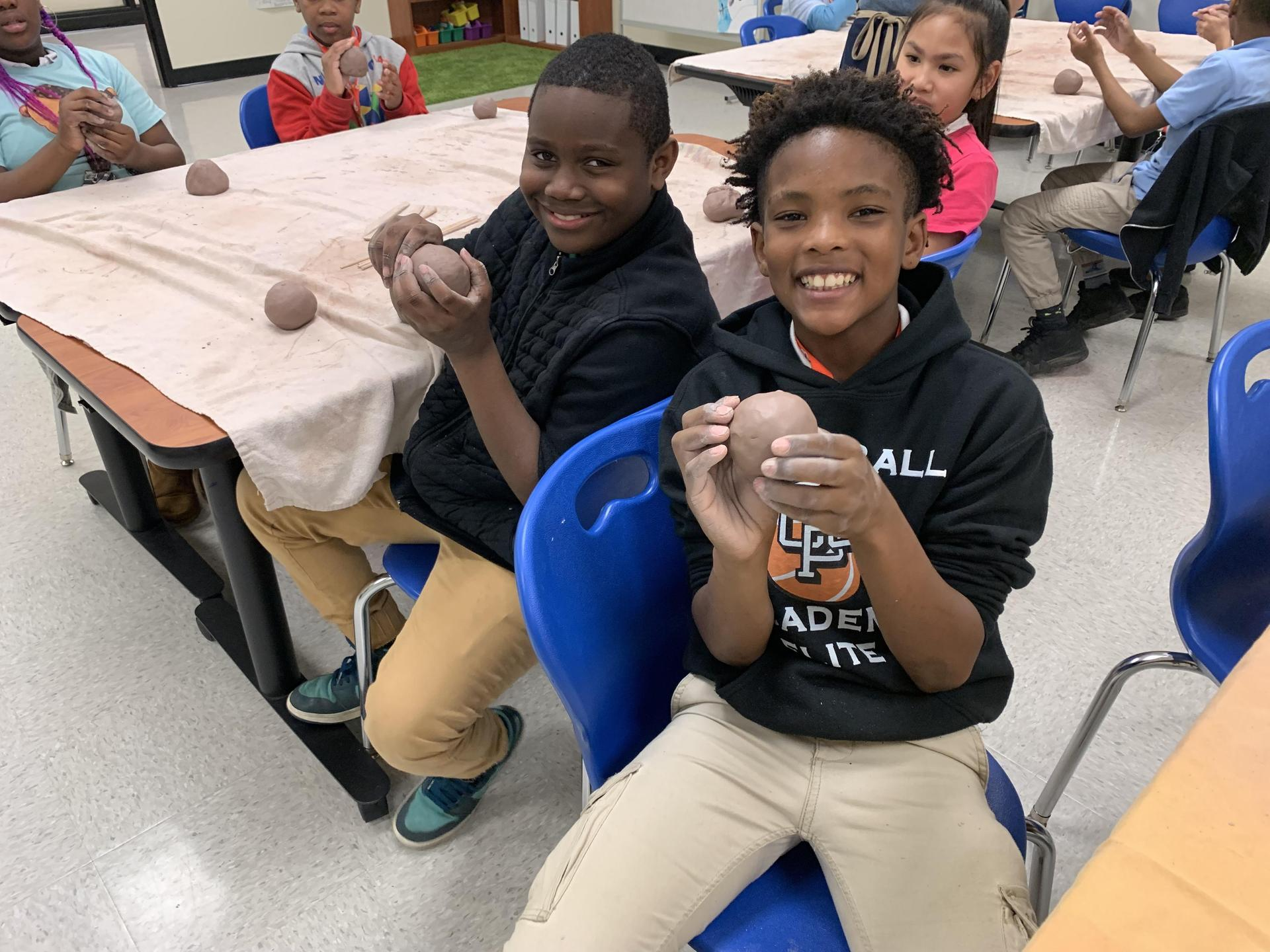 Two students working on clay mugs in art class